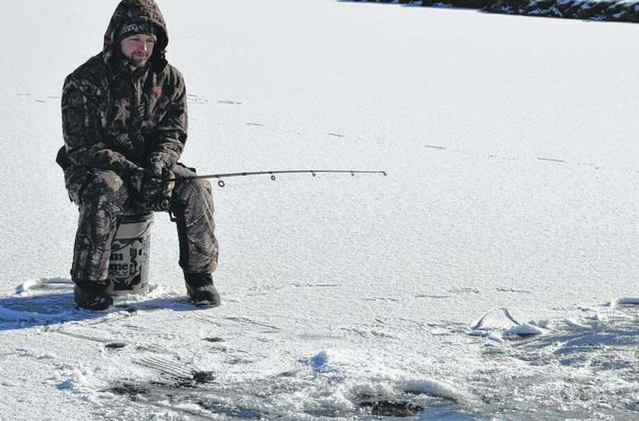 Martin Copeland of Jacksonville does a little ice fishing Saturday on Morgan Lake in Nichols Park. Photo: Samantha McDaniel-Ogletree | Journal-Courier