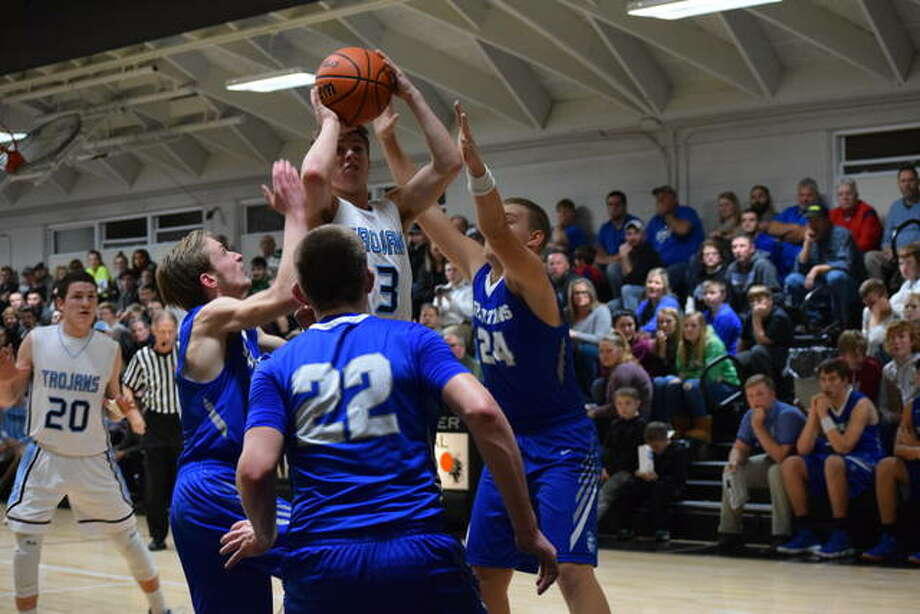 Triopia's Zach Thompson jumps over a crowd of Spartans for a shot during the first half at the Winchester Invitational. Photo: Audrey Clayton   Journal-Courier