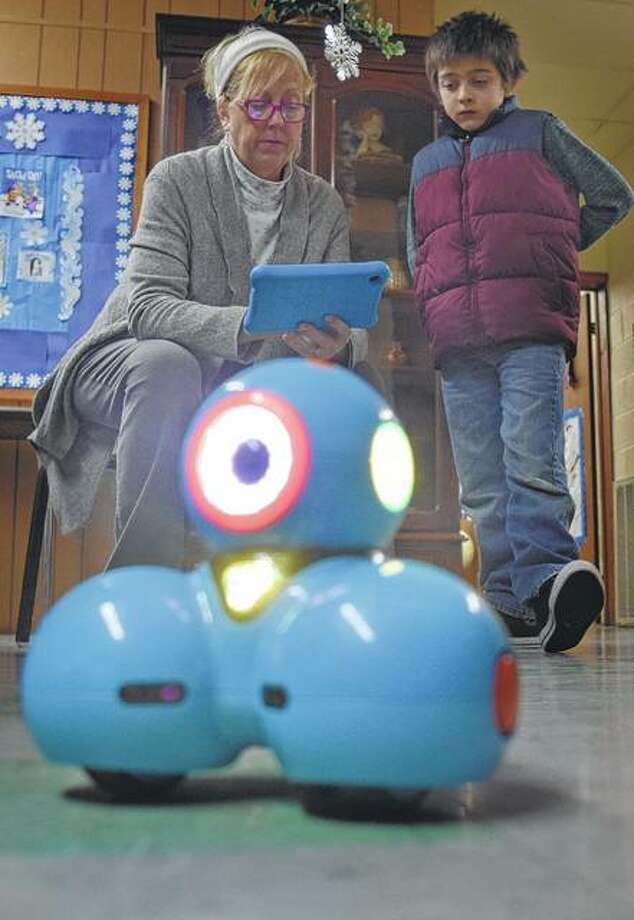 Robin Walker, marketing and events librarian at Brown County Public Library, shows Roan VanCleave, 9, of Mount Sterling the basics of the library's new robot.
