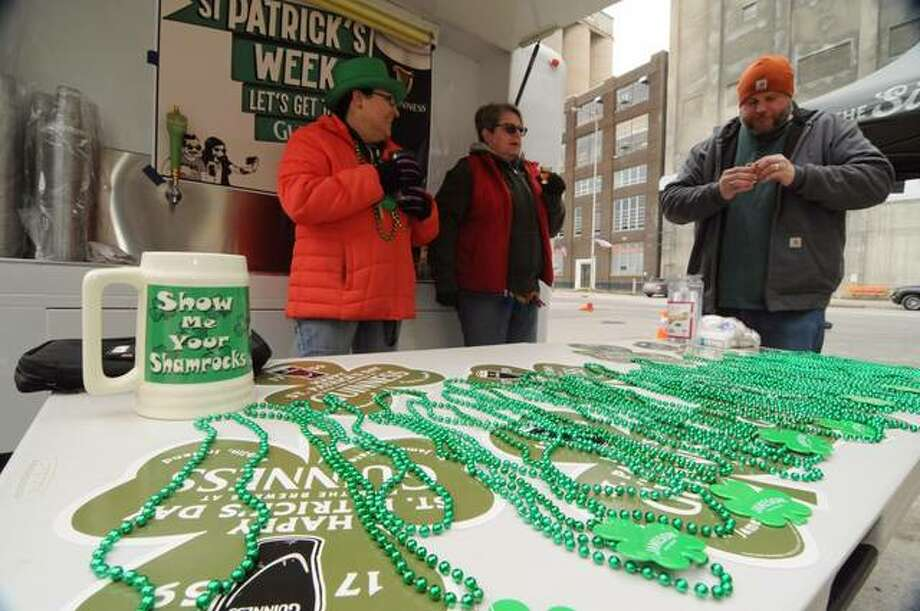 Mary Vankirk, left, owner of Morrison's Irish Pub, tends the beer wagon with Cindy and Mike Larson during Saturday's Downtown Alton St. Patrick's Festival.