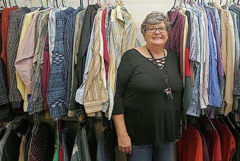 Pat Heinecke peers out from a row of clothes for sale at the Community for Christ Assistance Center in Camp Point. Heinecke, a former school teacher and principal, is the new director of the center. The center has a thrift store, food pantry and offers emergency rent and utility assistance. Phil Carlson | Quincy Herald-Whig (AP)
