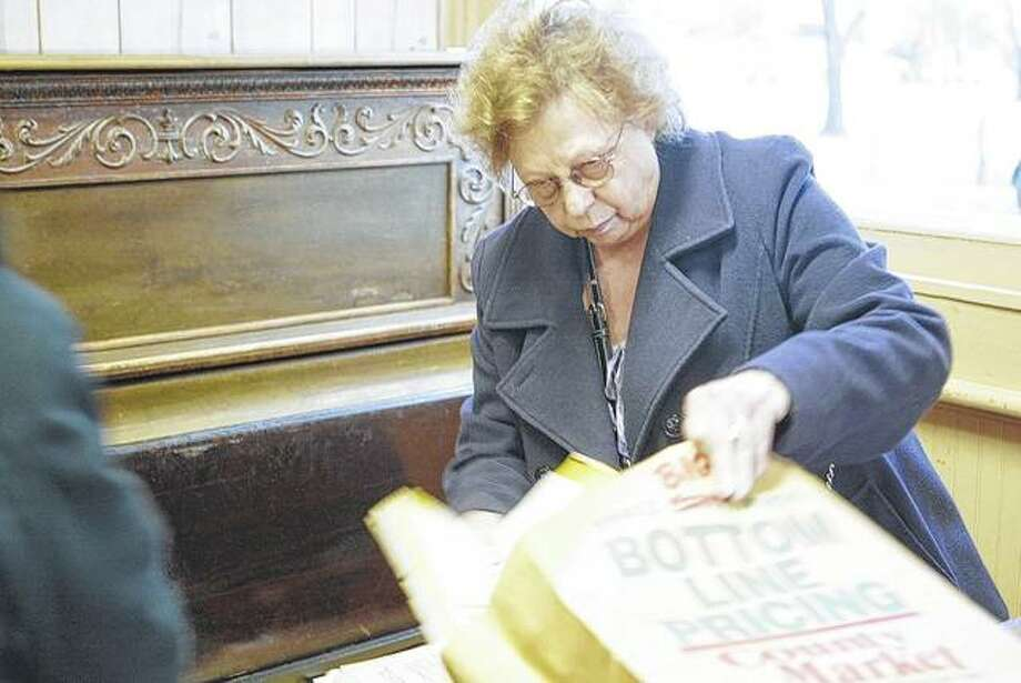 Lala Starner-Denny empties the contents of a piano bench in the Nortonville community hall. Photo: Samantha McDaniel-Ogletree | Journal-Courier