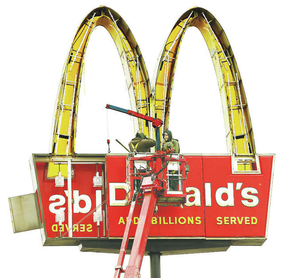 Employees of Piros Signs of Barnhart, Missouri, work from a tall bucket truck on the lighted golden arches sign for McDonald's on Illinois Route 3 in East Alton. The workers were removing the panels from the side of the sign to make repairs to the lighting system. Photo: John Badman | The (Alton) Telegraph