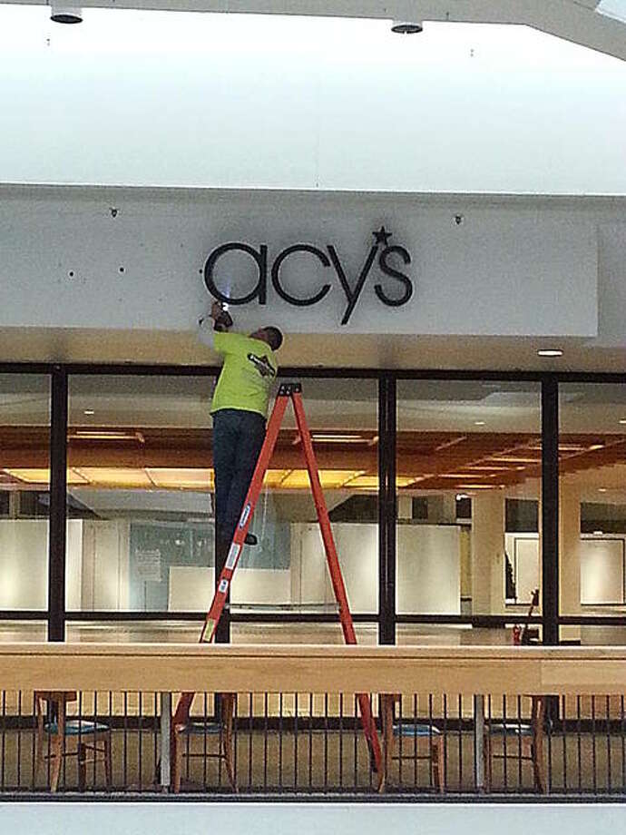 A worker Monday removes the Macy's sign from inside Alton Square Mall. Photo: For The Telegraph