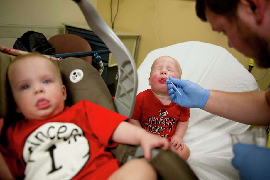 Kilian Daugherty, 1, gets his nose cavity swabbed for the flu by emergency department technician Jake Weatherford as his sister Madison, left, waits to be examined as well for flu symptoms at Upson Regional Medical Center in Thomaston, Ga., Friday, Feb. 9, 2018. The flu has further tightened its grip on the U.S. This season is now as bad as the swine flu epidemic nine years ago. A government report out Friday shows 1 of every 13 visits to the doctor last week was for fever, cough and other symptoms of the flu. That ties the highest level seen in the U.S. during swine flu in 2009. (AP Photo/David Goldman) Photo: David Goldman, STF / Copyright 2018 The Associated Press. All rights reserved.