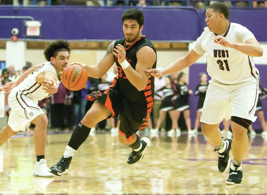 Edwardsville's AJ Epenesa splits the defense of Belleville West's Elijah Powell (left) and Tyler Dancy (right) during the Tigers sectional semifinal win last Tuesday at Collinsville. Epenesa and the Tigers saw their season end at 30-2 Tuesday night with a super-sectional loss to Chicago Simeon in Normal. Photo: Scott Kane | For The Telegraph