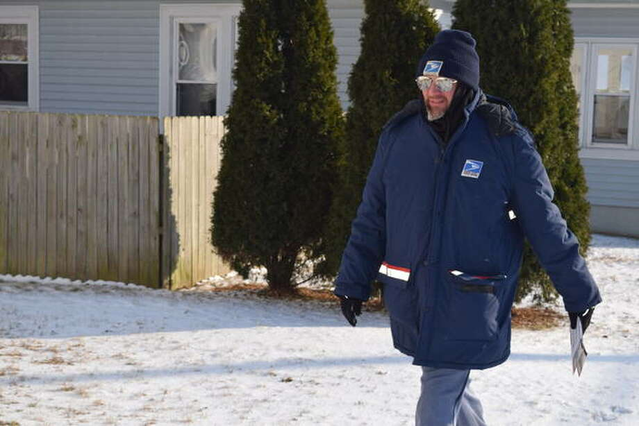 Jeff Hayes, a United States Postal Service mail carrier, makes his rounds Tuesday in Jacksonville, where temperatures were in the single digits. Photo: Nick Draper | Journal-Courier