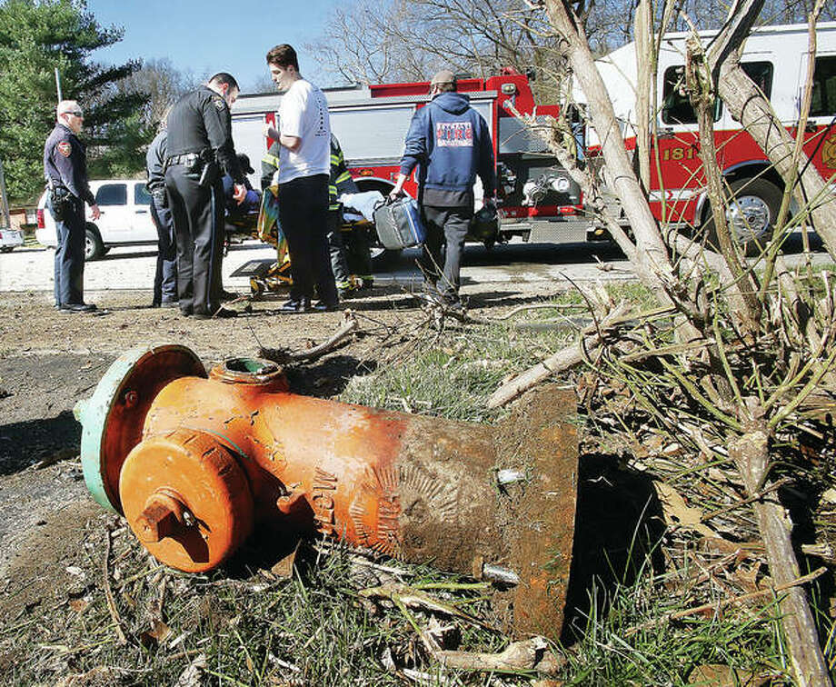 A fire hydrant, broken off from its base, lays on the ground Wednesday at Humbert Road and Valley Court in Alton as rescue workers prepare the driver of the Ford Explorer that hit it for transport to the hospital. The vehicle went on to destroy a tree, eject the driver and crack a utility pole at the scene. Photo: John Badman | The Telegraph