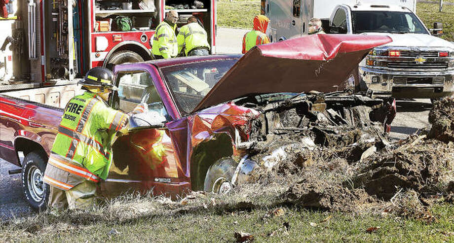 A Holiday Shores firefighter looks inside the full-size Chevrolet pickup truck that plowed into the embankment, right. Photo: John Badman | The Telegraph