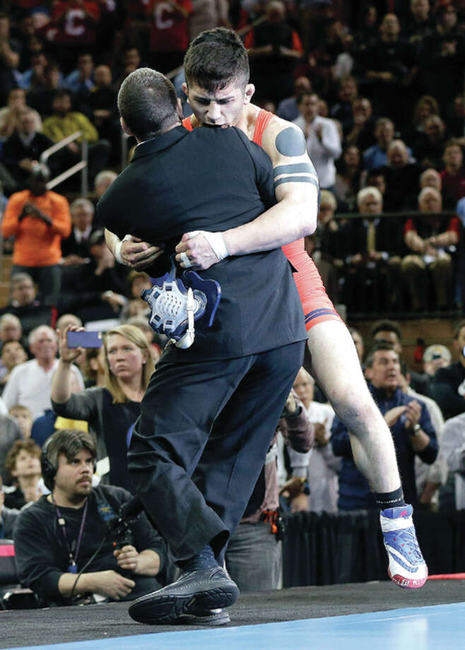 Illinois' Isaiah Martinez, right, hugs assistant coach Jeremy Hunter winning last season's 157-pound national title with a win over Penn State's Jason Nolf at Madison Square Garden in New York. Martinez is the top seed in the 165-pound weight class at this year's NCAA National Championships, set to start Thursday at the Scottrade Center in St. Louis. Photo: AP File Photo
