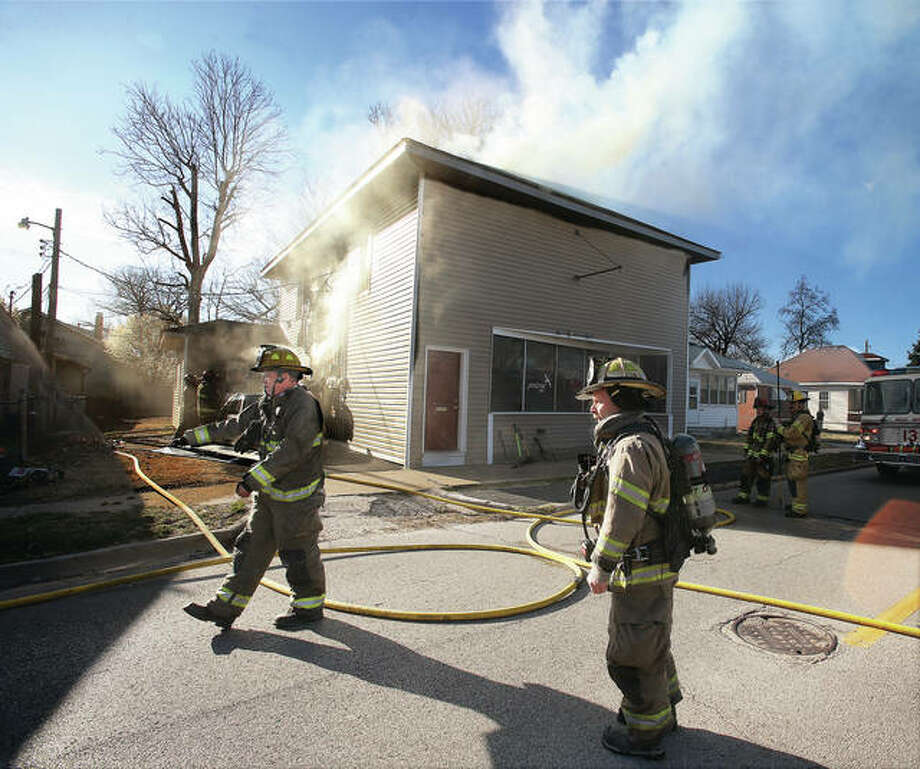 Smoke pours from the apartment building at 602 N. Wood River Ave. in Wood River Wednesday afternoon. Flames were climbing to the second floor from a downstairs apartment when firefighters arrived. Wood River called on East Alton, Roxana and Edwardsville for assistance. Photo: John Badman | The Telegraph