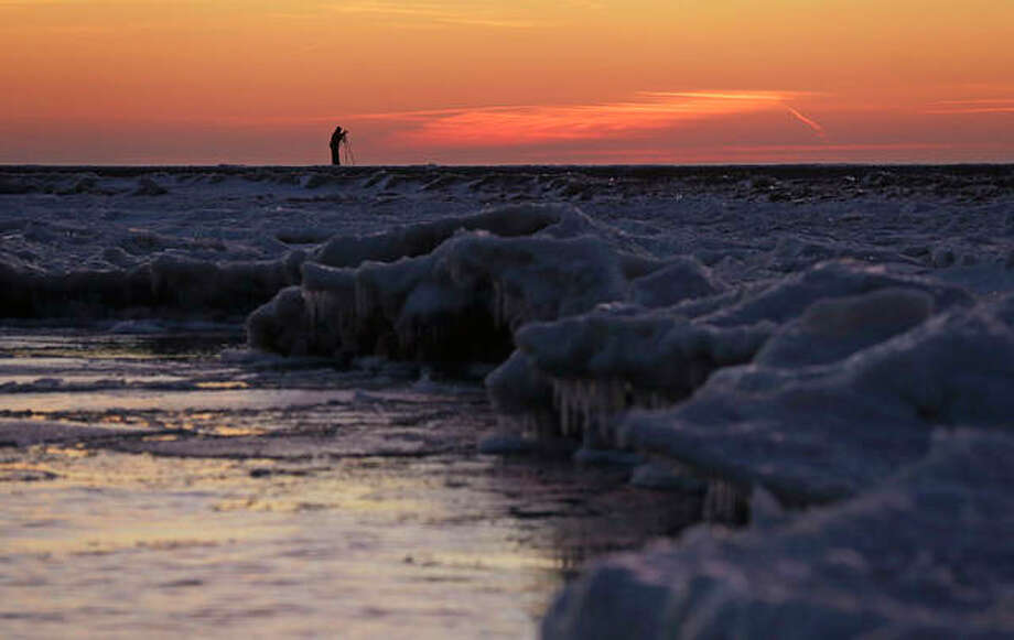 A photographer takes pictures of sunrise as ice forms along the shore of Lake Michigan before sunrise.