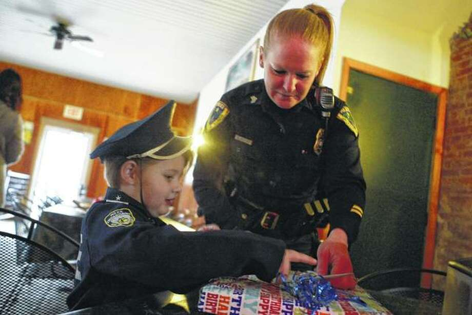 Sgt. Olivia Mefford helps Marcin Moody, 5 , open a birthday present from all of the first-responders in Jacksonville and South Jacksonville Saturday at Leo's Pizza.