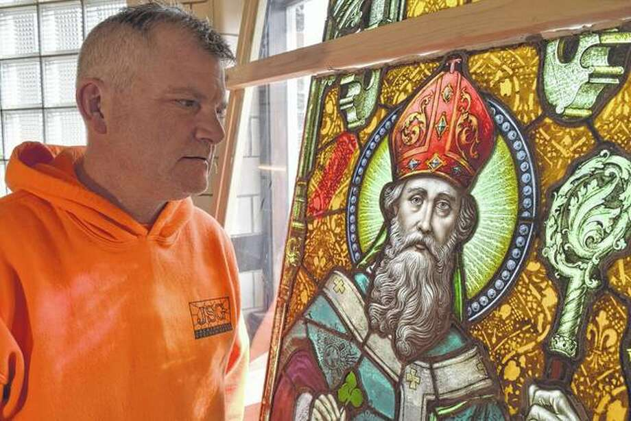 Ron Weaver, owner of Jacksonville Stained Glass, looks at a stained glass image of St. Patrick at the studio on East Morton Avenue. The image of St. Patrick is part of a window that Jacksonville Stained Glass artisans will soon restore and deliver to a Peoria customer.