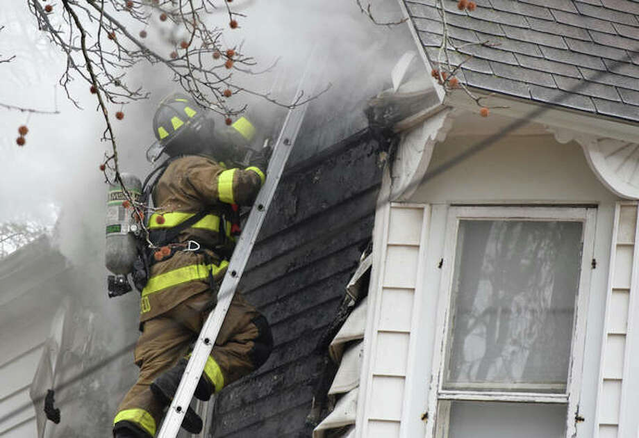 A Jacksonville firefighter checks on a fire in a house in the 100 block of West Chambers Street. Photo: Samantha McDaniel-Ogletree | Journal-Courier