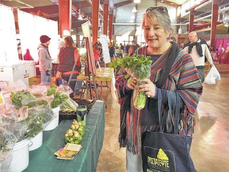 A shopper buys greens from Jon and Emma's Farm Booth during an indoor farmers market in December in Springfield. Jon and Emma, along with 15 other vendors, will sell their products during the Springfield Winter Farmers Market. Photo: Photo Provided