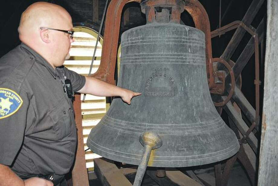 Morgan County Sheriff's Department Deputy Luke Tapscott, who serves as a courthouse bailiff, points out the name of the manufacturer of the 149-year-old bronze bell in the courthouse's clocktower. The bell, which weighs 4,000 pounds, was cast in 1869 in the A. Fulton's Sons & Co. foundry in Pittsburgh, Pennsylvania.