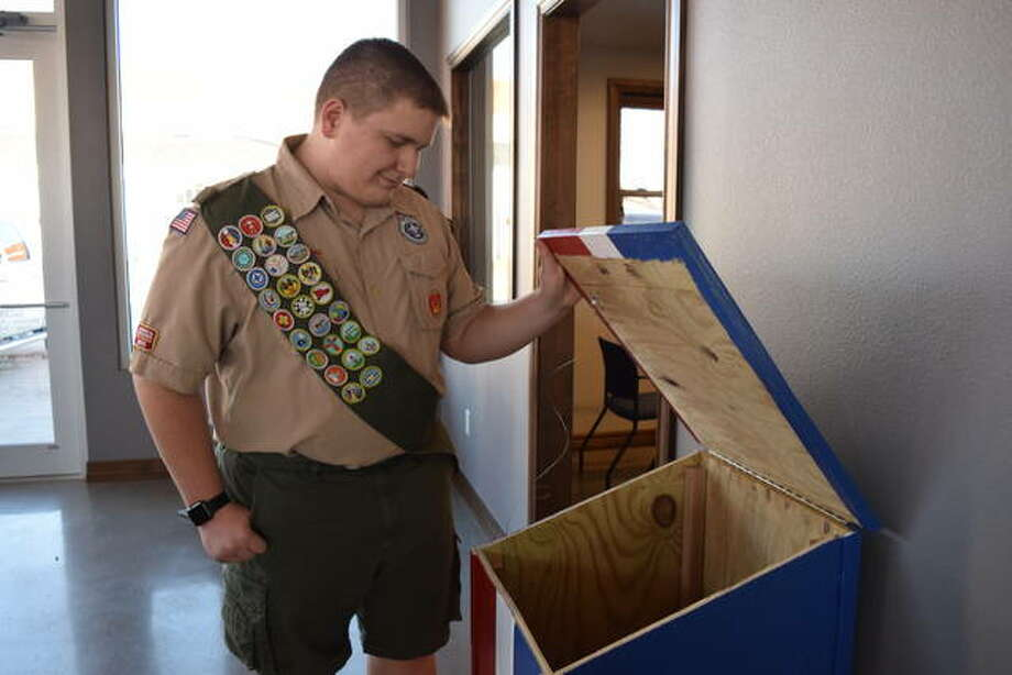 Chris Waid checks for flags in a box at Marshall Chevrolet in Winchester. Waid built the boxes as part of a service project as an Eagle Scout. Photo: Audrey Clayton | Journal-Courier