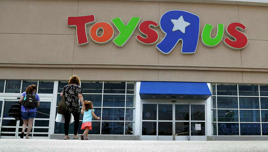 In this Sept. 19, 2017, file photo, shoppers walk into a Toys R Us store, in San Antonio. Toys R Us says it will be closing some U.S. stores and converting others to cobranded locations as it continues to deal with its financial restructuring following its bankruptcy filing. (AP Photo/Eric Gay, File)