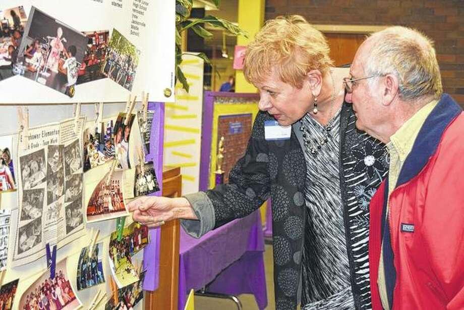 Sue Saunders, a former Eisenhower principal, and Bob McBride, a former PE teachers at Eisenhower, look at a historical timeline from Eisenhower Elementary School Wednesday during the elementary school's open house. Photo: Samantha McDaniel-Ogletree | Journal-Courier