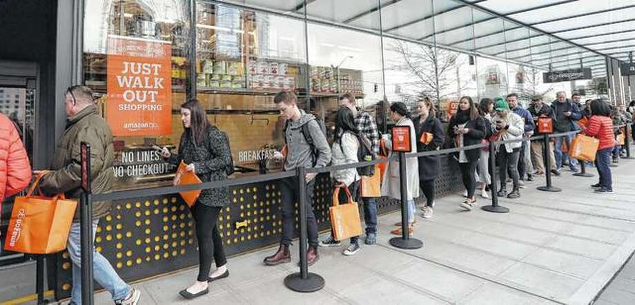 People stand Monday in a long line of shoppers waiting to get inside an Amazon Go store in Seattle. The store allows shoppers to scan their smartphone with the Amazon Go app at a turnstile, pick out the items they want and leave. Even before they got inside, many had their phones out and in use as they waited. Photo: Elaine Thompson | Associated Press