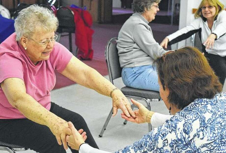 Darlene Sills (left) of Jacksonville warms up as a part of the Joy of Movement, Parkinson's Dance and Exercise class with instructor Eve Fischberg.