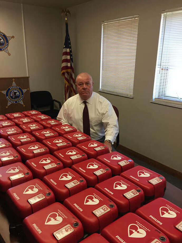 Madison County Sheriff John Lakin with just a few of the department's 53 defibrillators now in service.
