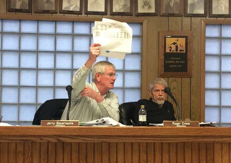Alderman Jerry Bauersachs holds up financial printouts while trying to demonstrate why the city was not running a deficit. He later dropped his argument, after a citizen pointed out his figures were off by half-a-million dollars.