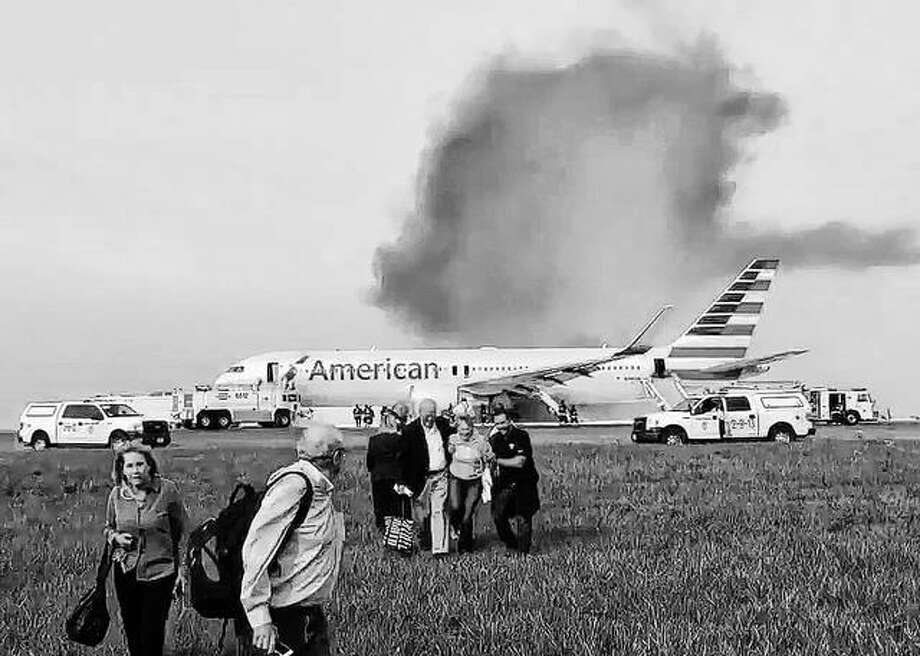 Passengers walk away from a burning American Airlines jet that aborted takeoff and caught fire on the runway at Chicago's O'Hare International Airport last year. Investigators say communication problems between flight attendants and pilots put evacuating passengers at more risk after the plane caught fire. The National Transportation Safety Board said Tuesday that flight attendants didn't know how to use the intercom system to speak with pilots before they directed passengers to use an emergency exit behind an engine that was still running. Jose Castillo | Via AP