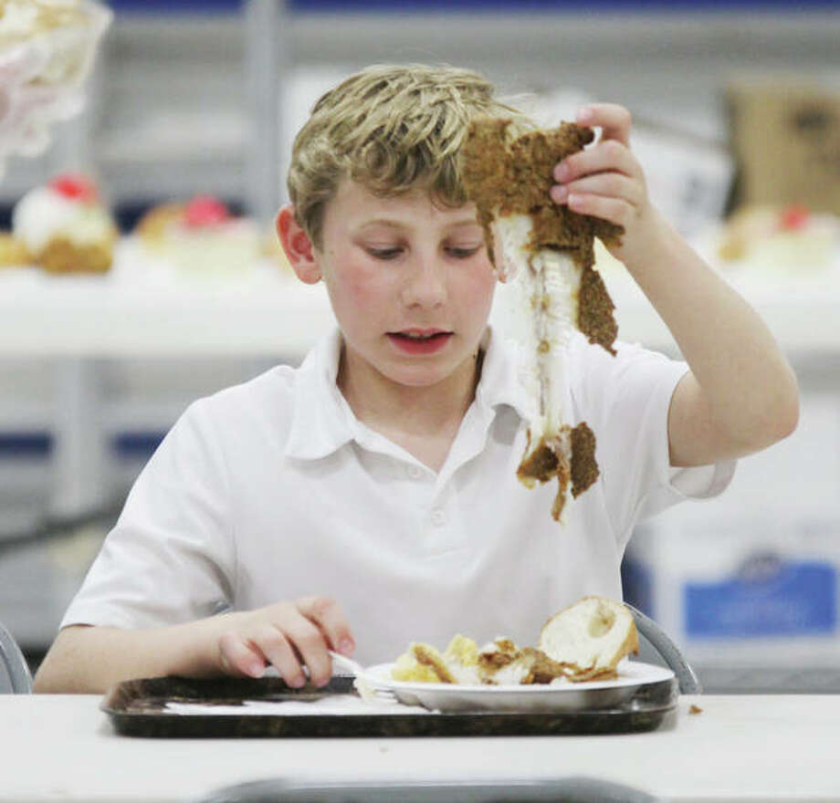 Nicholas Werts, 10, a sixth-grader at Our Lady Queen of Peace School in Bethalto, holds up catfish bones after stripping them during the church and school's weekly Lenten fish fry Friday afternoon. On a typcial Friday they will serve approximately 350 people.