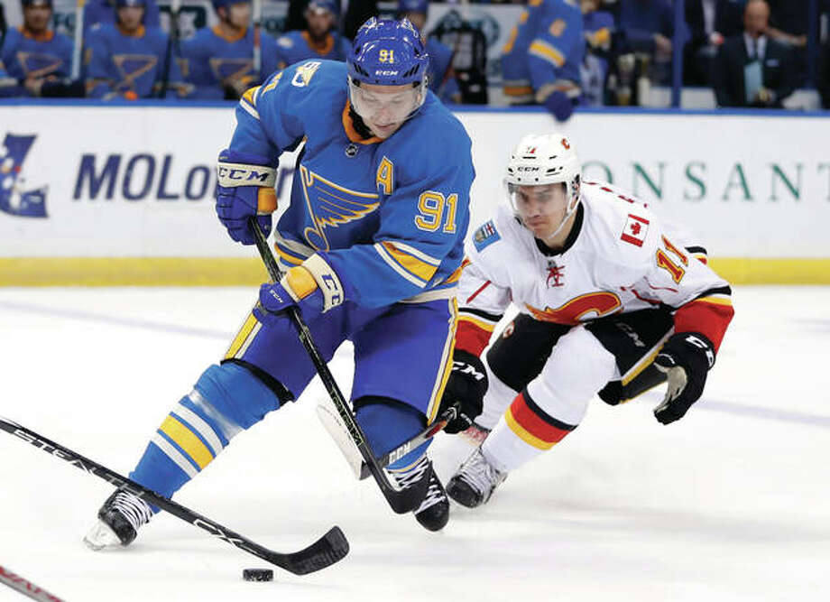 The Blues' Vladimir Tarasenko controls the puck as the Flames' Mikael Backlund (right) lunges toward the puck during the second period Saturday night in St. Louis. Photo: Associated Press