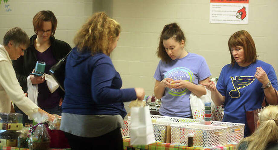 Attendees of Olde Alton Arts and Crafts Fair peruse one of the 100 booths that packed the hallways of Alton High School Saturday. The annual event, including a pancake breakfast, raised approximately $2,500 for the Alton Band and Orchestra Builders program.