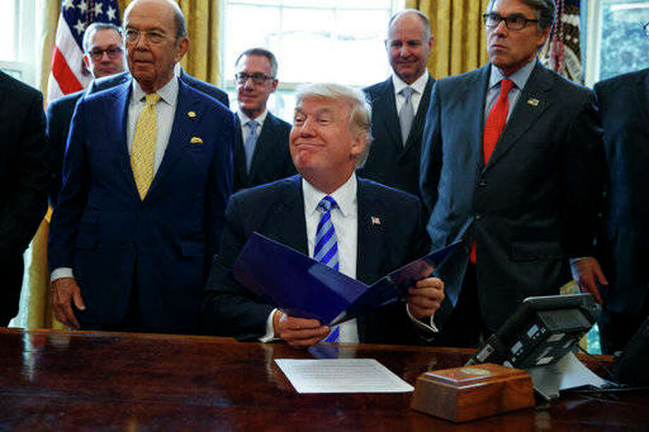 President Donald Trump, flanked by Commerce Secretary Wilbur Ross, left, and Energy Secretary Rick Perry, is seen in the Oval Office of the White House in Washington Friday, March 24, 2017, during the announcing of the approval of a permit to build the Keystone XL pipeline, clearing the way for the $8 billion project. Photo: (AP Photo/Evan Vucci)