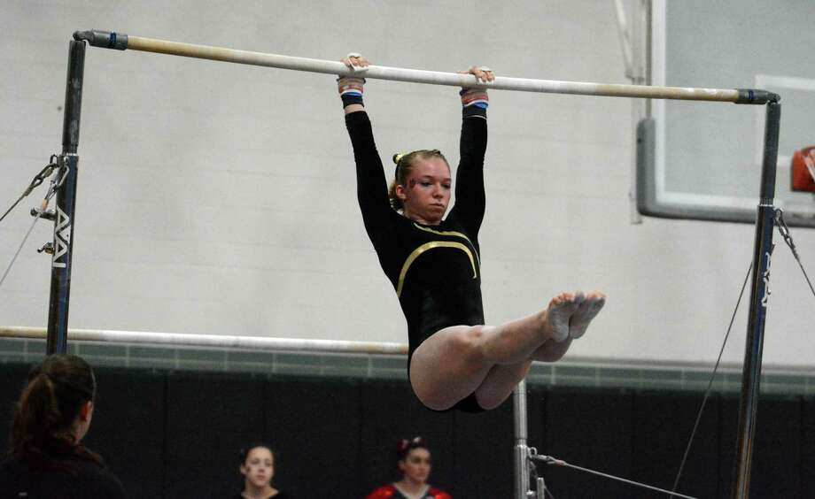 Hand's Erin Naclerio competes on the uneven bars during the SCC championship meet. Photo: Dave Phillips / For Hearst Connecticut Media