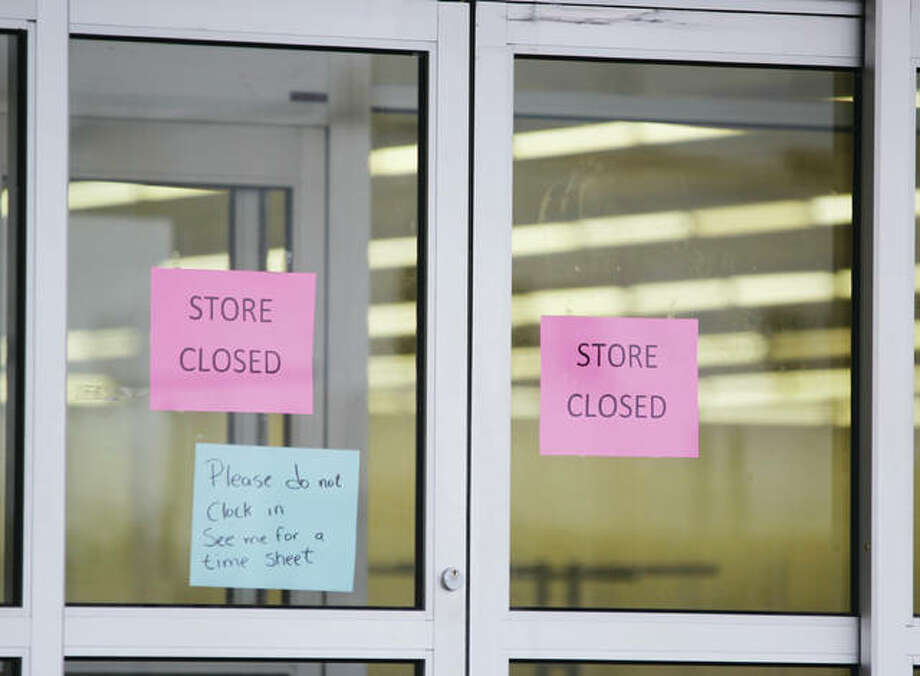 Signs at the front entrance of the former Kmart Store highlight the recent closing of the store, located in the Seminary Plaza Shopping Center, 2851 Homer M Adams. Company officials announced January 4 that the store was among two in Madison County closing as part of a restructuring by the company. Some workers appeared to be cleaning up inside the building Tuesday afternoon. Photo: Scott Cousins | The Telegraph