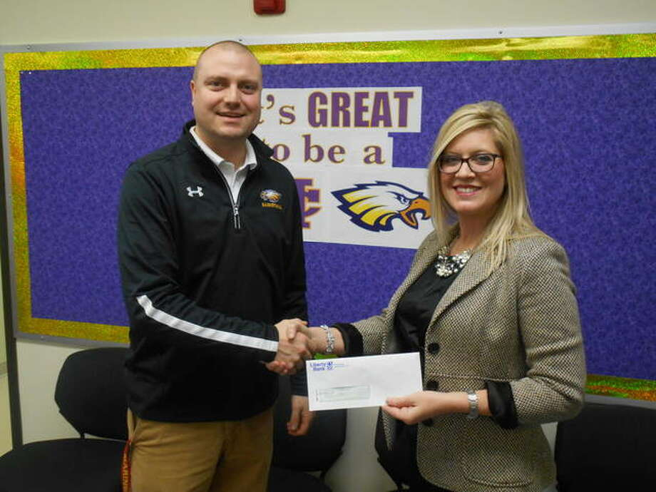Liberty Bank's Michelle Zimmer, right, presents a check to Civic Memorial High School Athletic Director Adam Miller. Photo: For The Telegraph