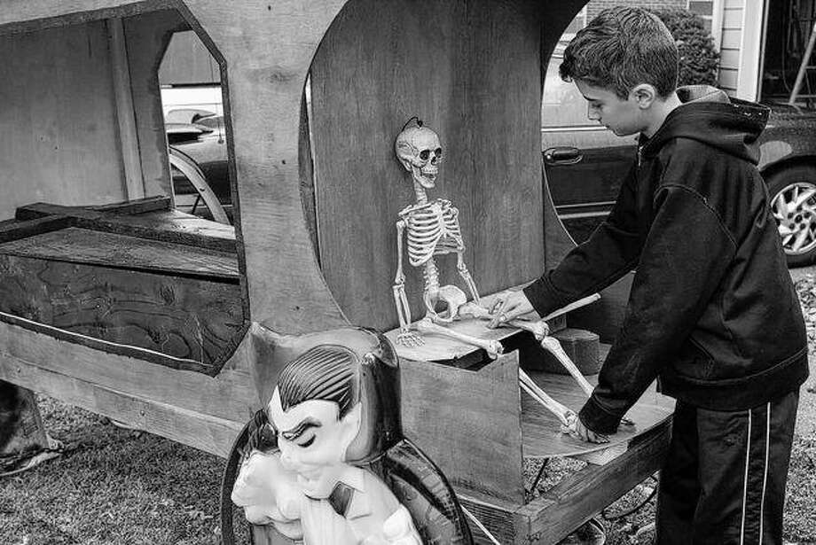 """Jacob Wyman, 11-year-old son of Doug and Christy Wyman of South Jacksonville, makes some adjustments Saturday to a Halloween skeleton sitting on a homemade hearse in the Wyman family's front yard. The Wyman family display also included a replica of the front of a Gothic church and numerous lighted pumpkins, Frankenstein, Dracula and a ghost. There also were gravestones and a 12-foot inflatable pumpkin Scrooge. """"Me and my dad worked on the display for the past month,"""" Jacob said. """"The thing I enjoyed most was getting to use power tools to make the hearse and the church."""" Photo: Greg Olson 