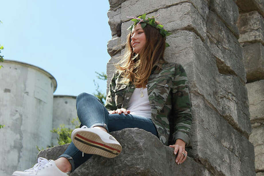 Jessica Biel sits on a stone wall at the site of the former Alton Prison.