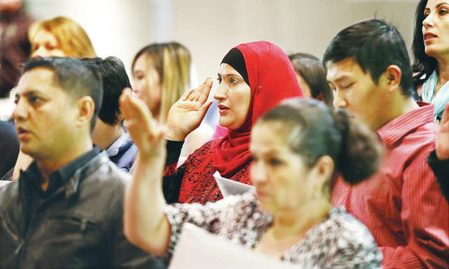 A woman from Iraq, center, was among 47 people from 20 countries who took the oath of citizenship Wednesday at Alton High School in Godfrey during a United States Naturalization Ceremony held by the U.S. District Court, Southern District of Illinois.