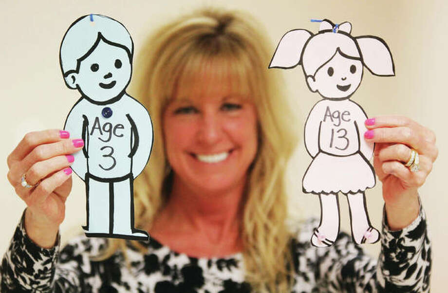 Julie Eberhart, office manager at the Madison County Child Advocacy Center, holds up two of the cutouts that will adorn the Madison County Administration Building at part of Child Abuse Prevention Month. Each cut-out represents an actual child interviewed at the CAC, which provides a neutral place for investigators to interview children about physical, sexual or mental abuse and neglect. In 2016, 634 interviews were held at the office, which is currently undergoing an expansion because of the increasing numbers of interviews. Photo: Scott Cousins | The Telegraph