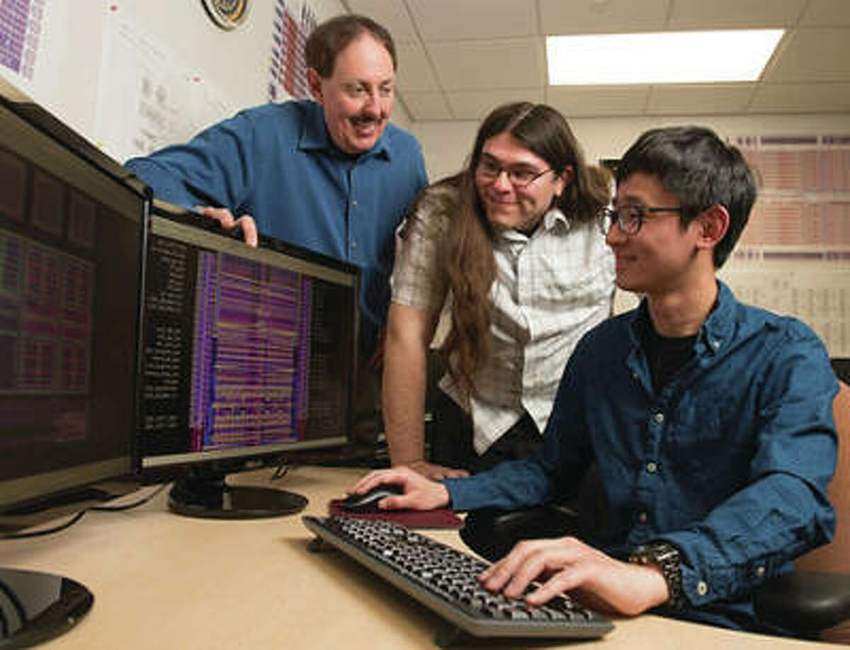 SIUE Graduate student Pohan Wang, of Taiwan, is seated in the research lab, with fellow student Bryan Orabutt, of Springfield, Illinois, middle, and Professor George Engel, left, looking on.