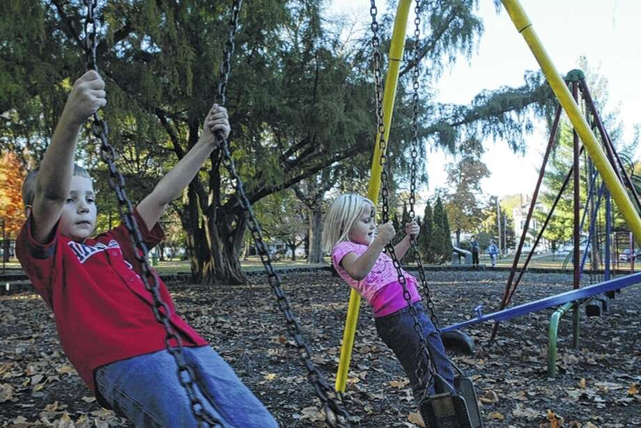 Seven-year-old Brayden Vann (foreground) and his 3-year-old sister, Brooke Vann, enjoy Tuesday's unseasonably warm temperatures by playing on the swings in Duncan Park. They are the children of Dawn and Chris Vann of Jacksonville. Photo: Greg Olson | Journal-Courier