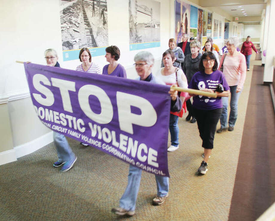 Marchers walk around the upper level of Alton Square during the 3rd Annual Domestic Violence Awareness Walk. About 75 people participated in the event, which raises both awareness and funds for local domestic violence prevention and victim assistance efforts.