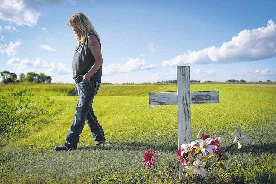 Renee Jones Schneider | Minneapolis Star Tribune (TNS) Gayle Lund walks by a cross she put in the spot on her driveway where her 24-year-old son Jake Fuglie died in a tractor rollover in 2010. He was driving his grandfather's old tractor to plow snow and it tipped on the small incline of the grass by the driveway.