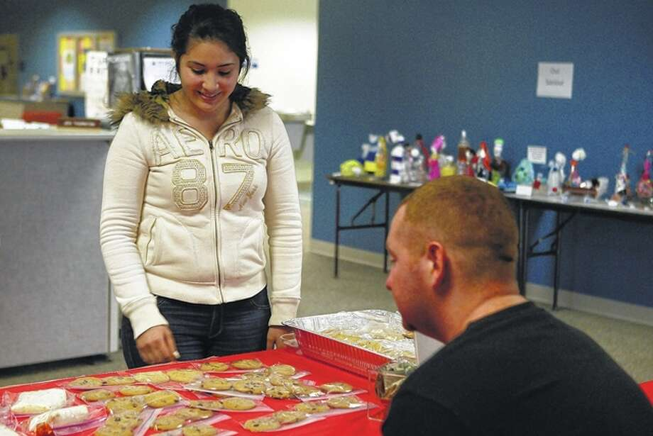 Edith Chaidez, a sophomore at Lincoln Land Community College, looks at the baked goods for sale at the college to raise money to send a Morgan County child to Disney World. Photo: Samantha McDaniel-Ogletree | Journal-Courier