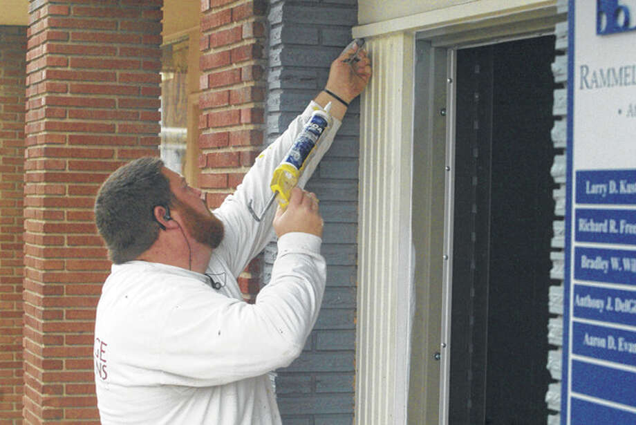 Paul Wellhausen of J.B. Large & Sons Painting repairs a door frame at the Rammelkamp Bradney Attorneys at Law office on West State Street. Photo: Nick Draper | Journal-Courier