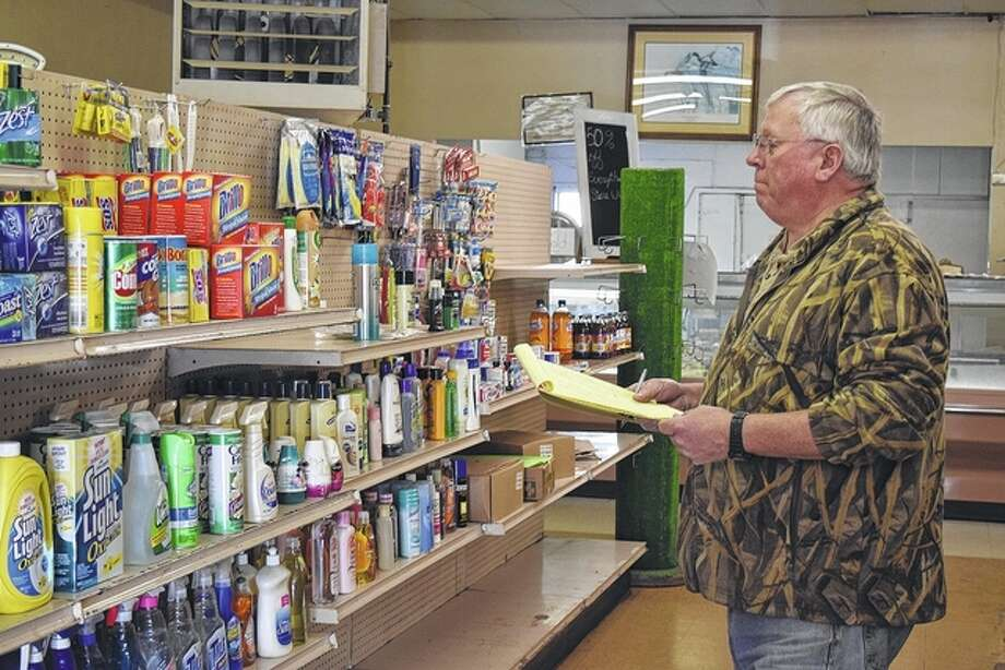 Flynns Riverside Market owner and operator Steve Flynn takes one of his final inventories Friday at the longtime Meredosia grocery store, which will close its doors for good at 5 p.m. today. Photo: Greg Olson | Journal-Courier