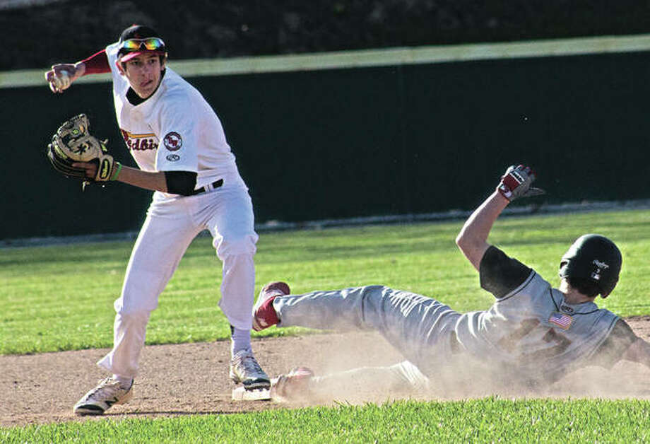 Alton shortstop Brandon Droste (left) makes a throw to first base after getting a force at second during a Southwestern Conference baseball game against Granite City on Friday at Alton High in Godfrey. Photo: Nathan Woodside / For The Telegraph