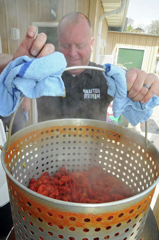 Grafton Oyster Bar owner Brad Hagen lifts crawfish out of the cooking kettle to serve customers at the restaurant's Crawfish Festival on Sunday.