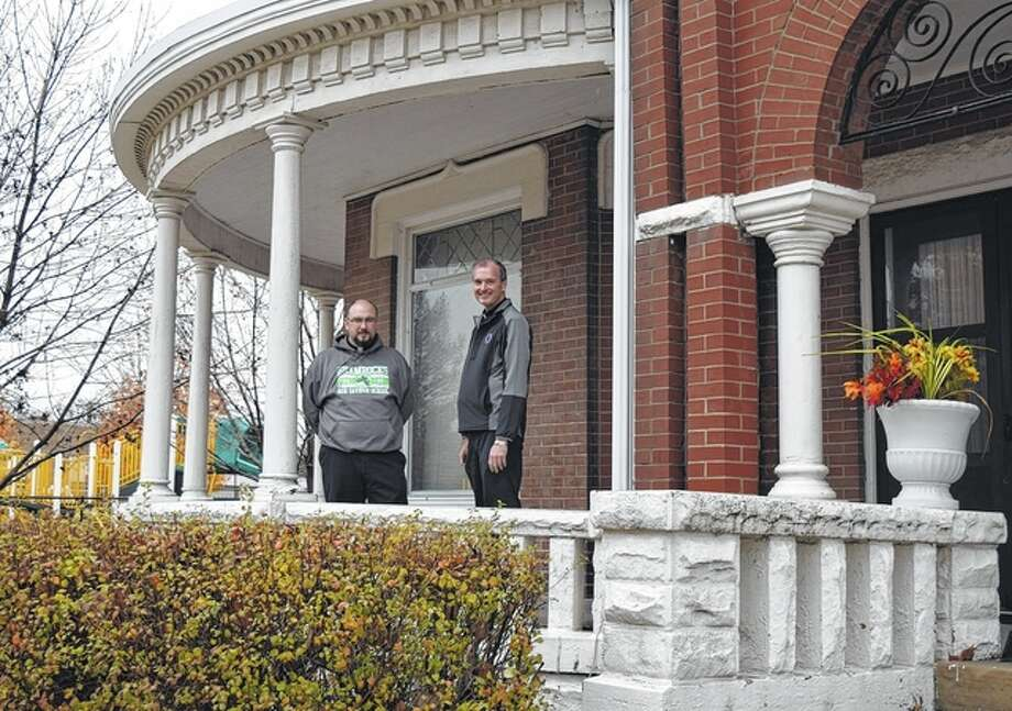 The Revs. Hyland Smith (left) and Tom Meyer, pastor of Our Saviour Parish, stand on the front porch of the parish's old rectory. Smith, Meyer and the Rev. Samuel Bagyo Jr. will move into the old rectory Jan. 1. It's been 20 years since the building housed the parish's priests.